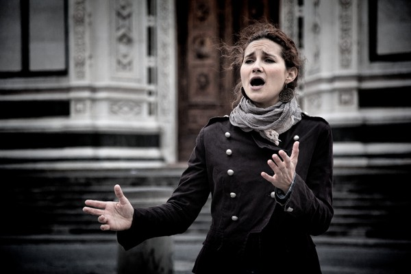 Young woman singing opera in front of the Basilica of Santa Croce in Florence.